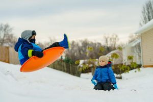 Kid in sled in the air as another child is kneeling and watching