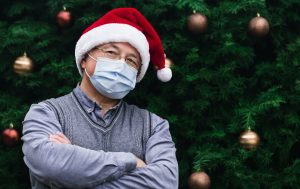 Person with face mask wearing Santa Hat in front of a tree
