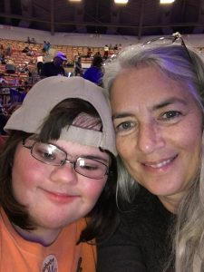 Picture of mom and daughter. Daughter has dark hair and is wereaing a baseball cap. Mom has gray hair with a purple highlight.