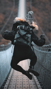 Young woman in dark coat wearing a back pack clicking her heels while crossing a foot bridge