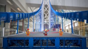 Large blue suspension bridge made out of legos with two lego construction workers figures and one lego supergirl figure standing on the bridge