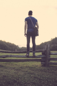 Young man wearing a blue shirt with a satchel standing on a the middle rail of a wooden fence looking into the sunset