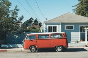 Orange VW van outside small blue house